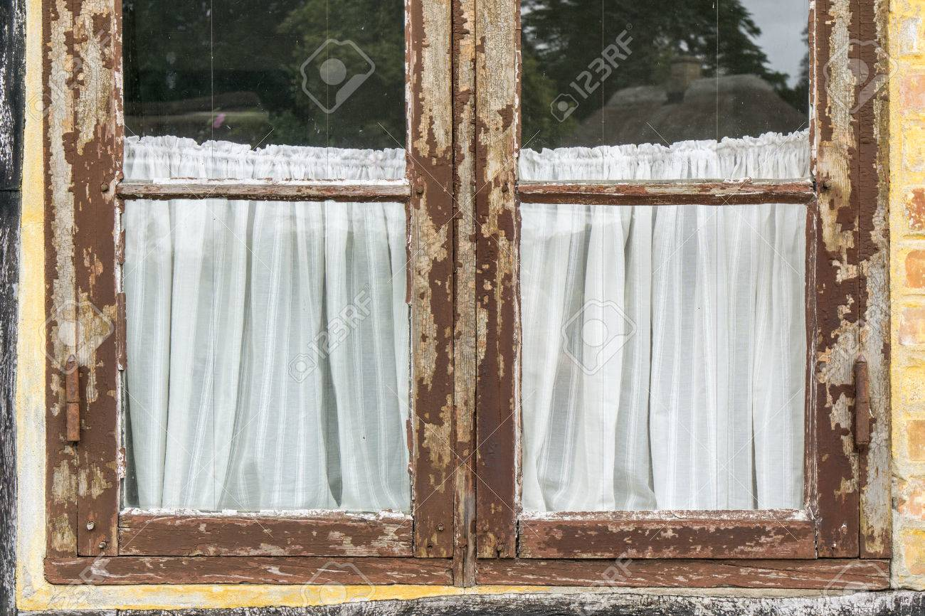 Part Of Old Vintage Window With Brown Cracked Paint And White Retro Curtains Stock Photo