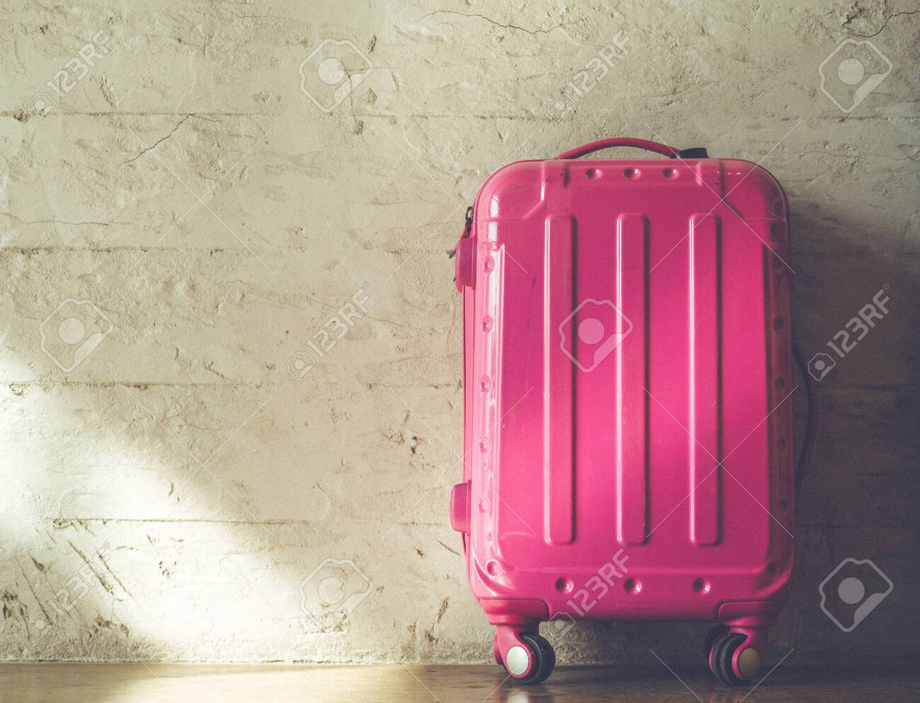Pink suitcases on brick wall background - 120610935