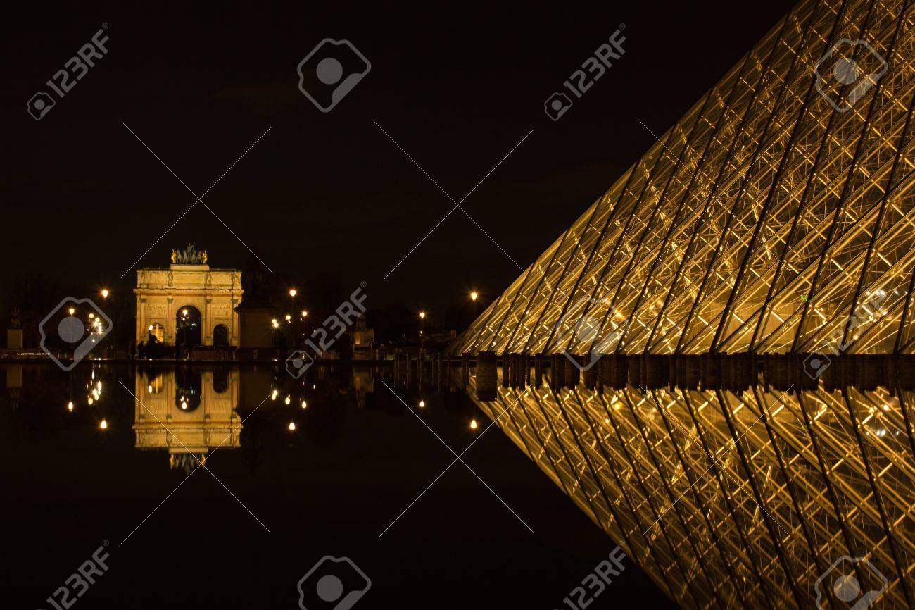 PARIS,FRANCE - NOVEMBER 05: Entrance to Louvre Museum and Arc de Triomphe du Carrousel on November 05, 2012 in Paris. The crystal pyramid was completed in 1989, it has become a landmark of of Paris. Stock Photo - 17838447