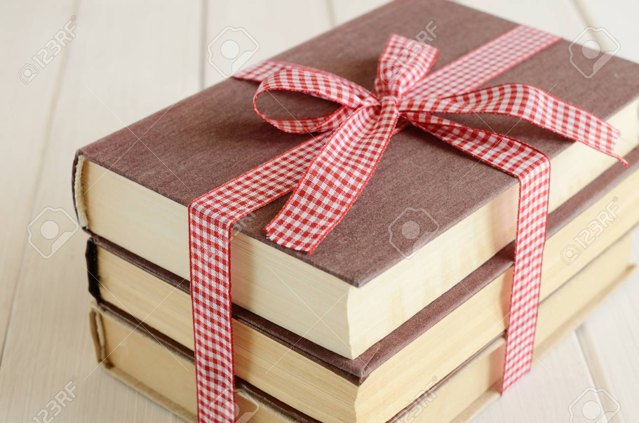 Pile Of Books Bounded Up In Red-and-white Ribbon On White Wooden ...