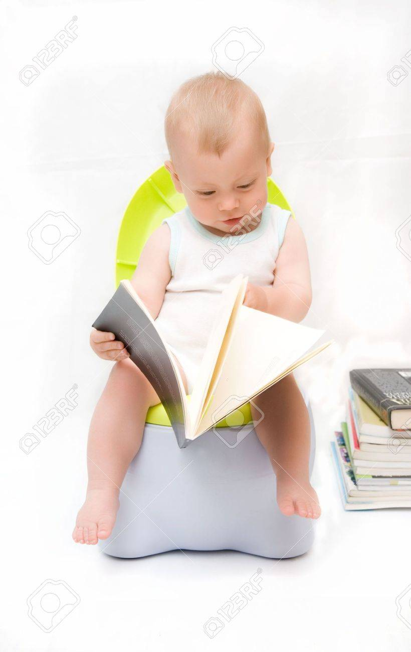 The little boy sits on a chamber-pot and reads the book Stock Photo - 5038087