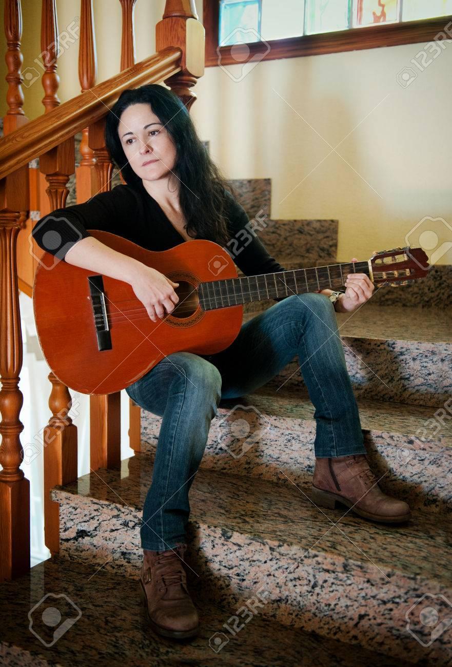 Pretty sad woman playing a guitar stock photo 30537683