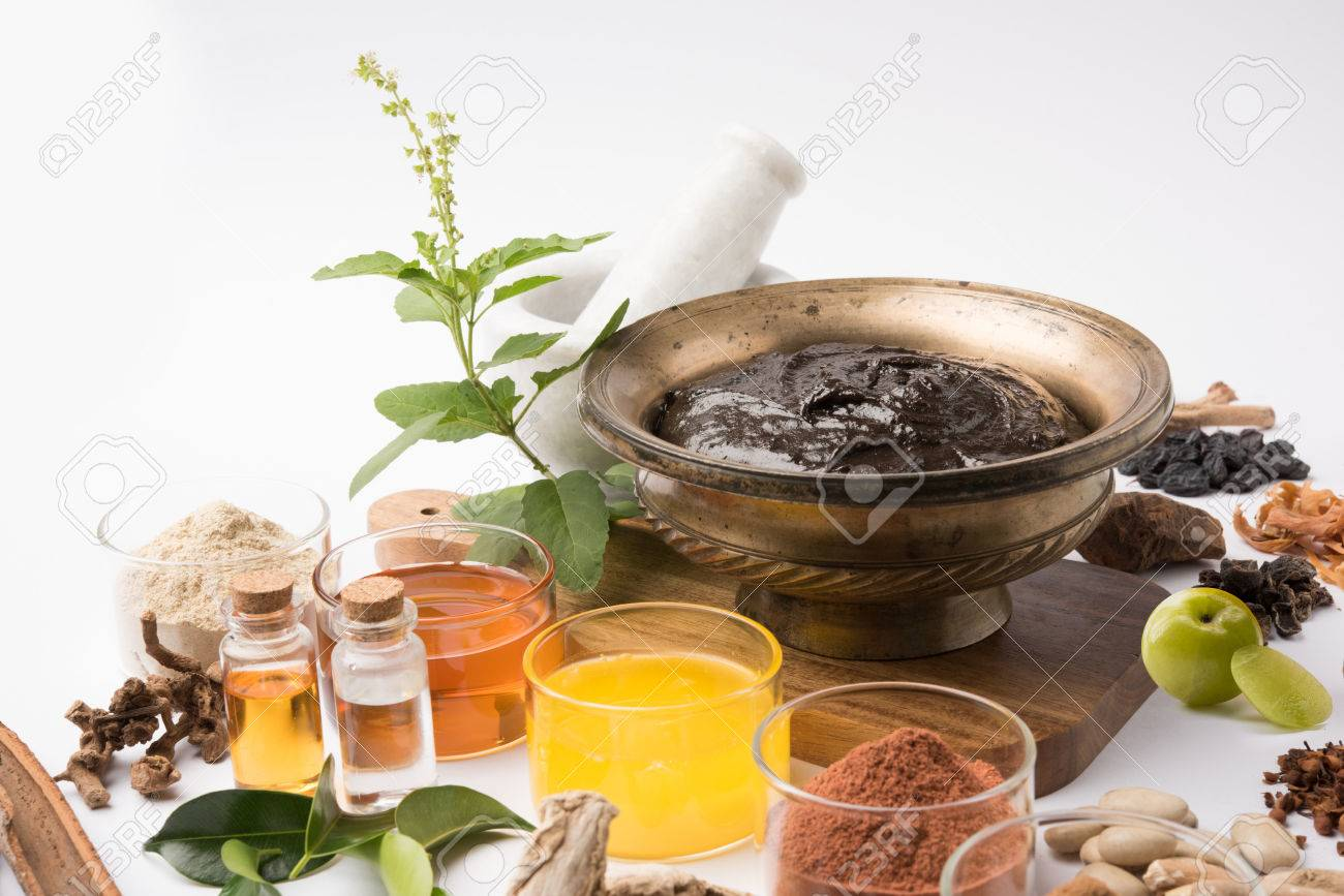 Top view of a bowl of Chyawanprash, an Indian Ayurvecid dietary supplement, with the ingredients laid around it, on a white background. - 80628096