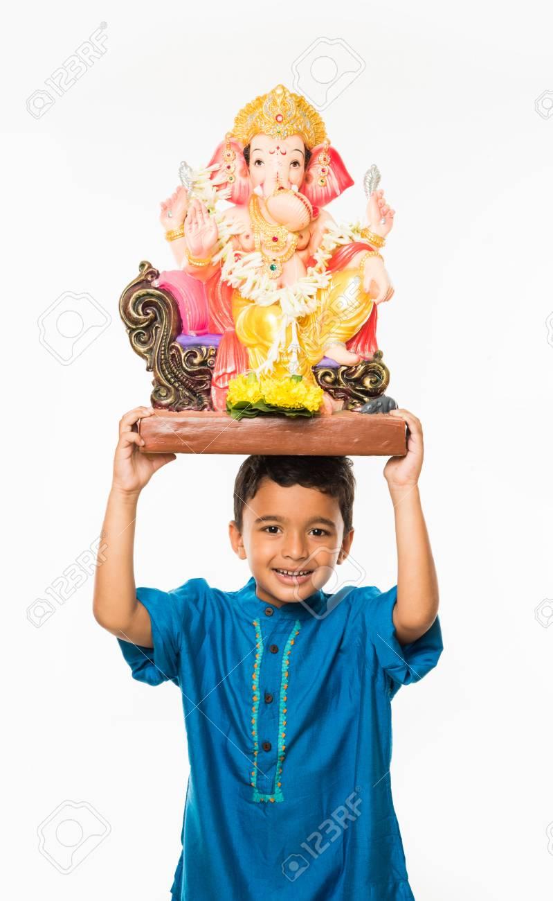 portrait of cute little indian boy holding a ganesh idol or lord