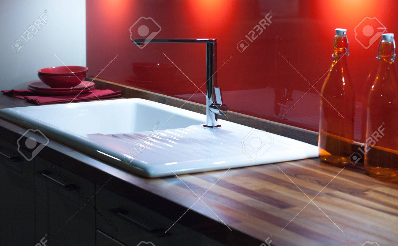 Modern Stylish Kitchen With Wooden Counter, White Enamel Sink And Modern  Silver Faucet Tap Stock