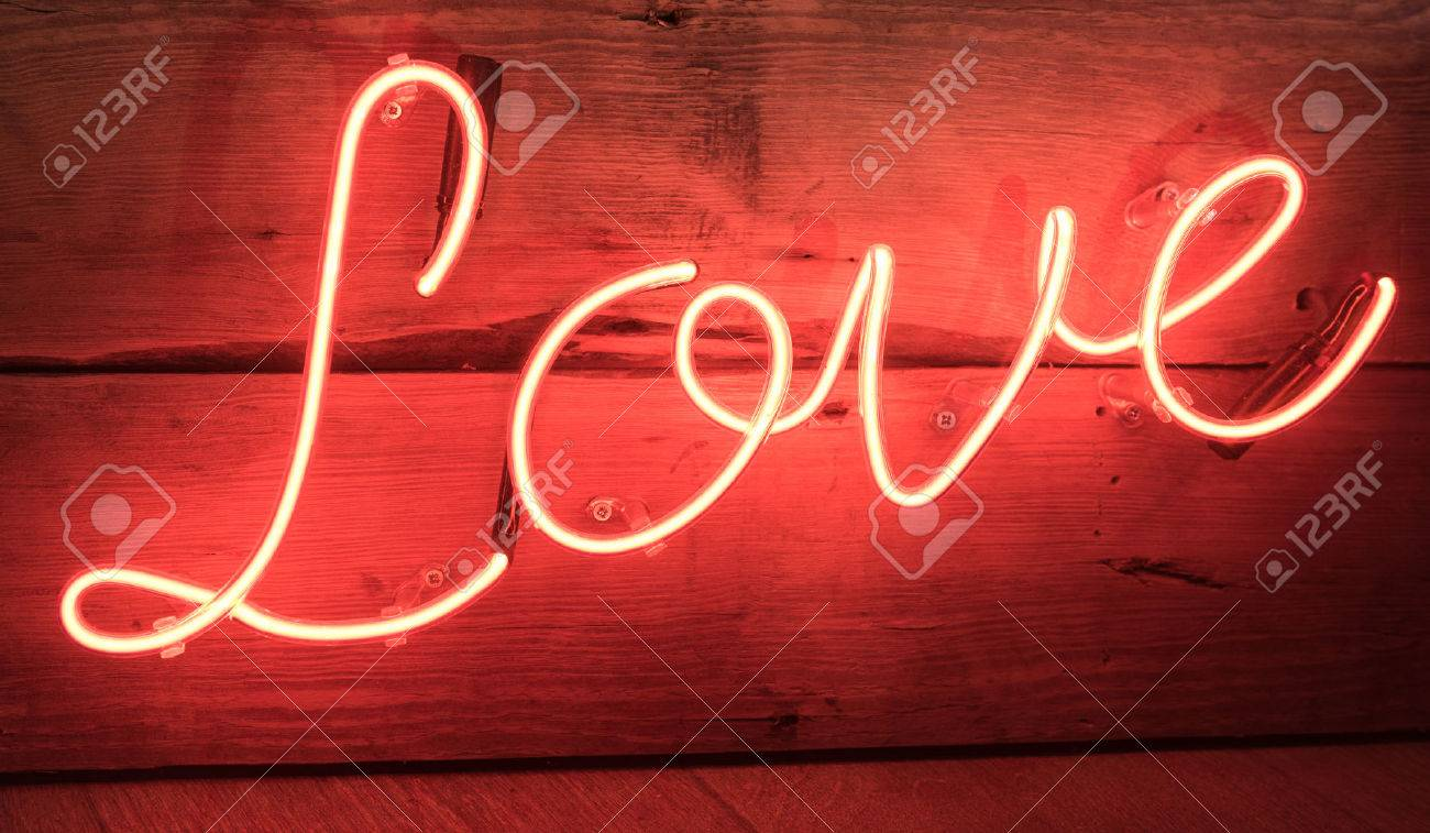 red neon love sign with wooden background stock photo, picture and