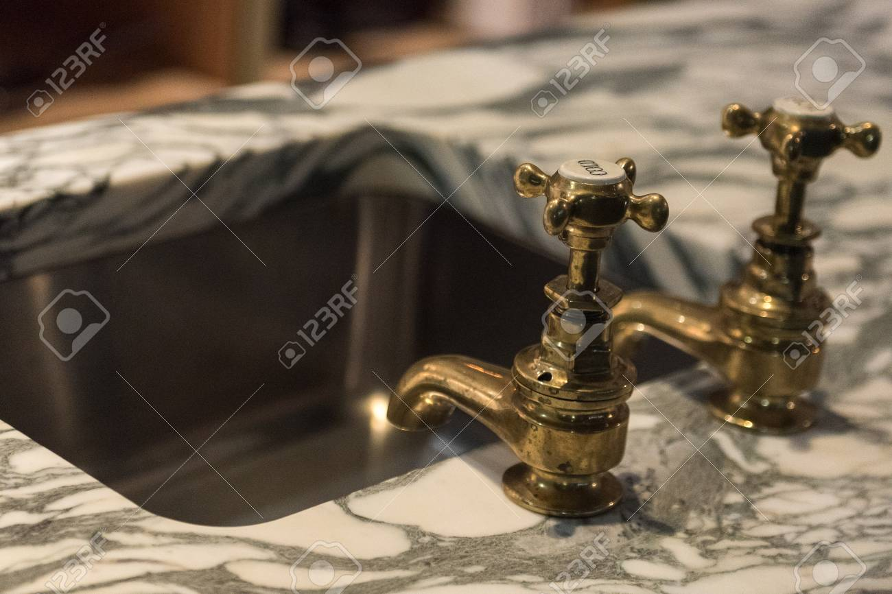 Stylish Brass Faucets And Luxury Marble Basin Sink Stock Photo ...