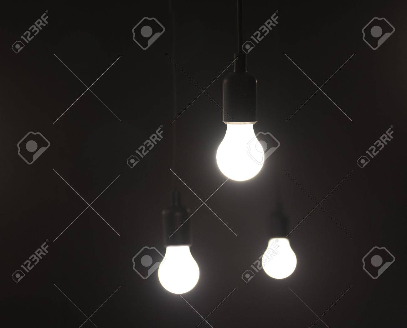 three light bulbs hanging with plain simple background stock photo
