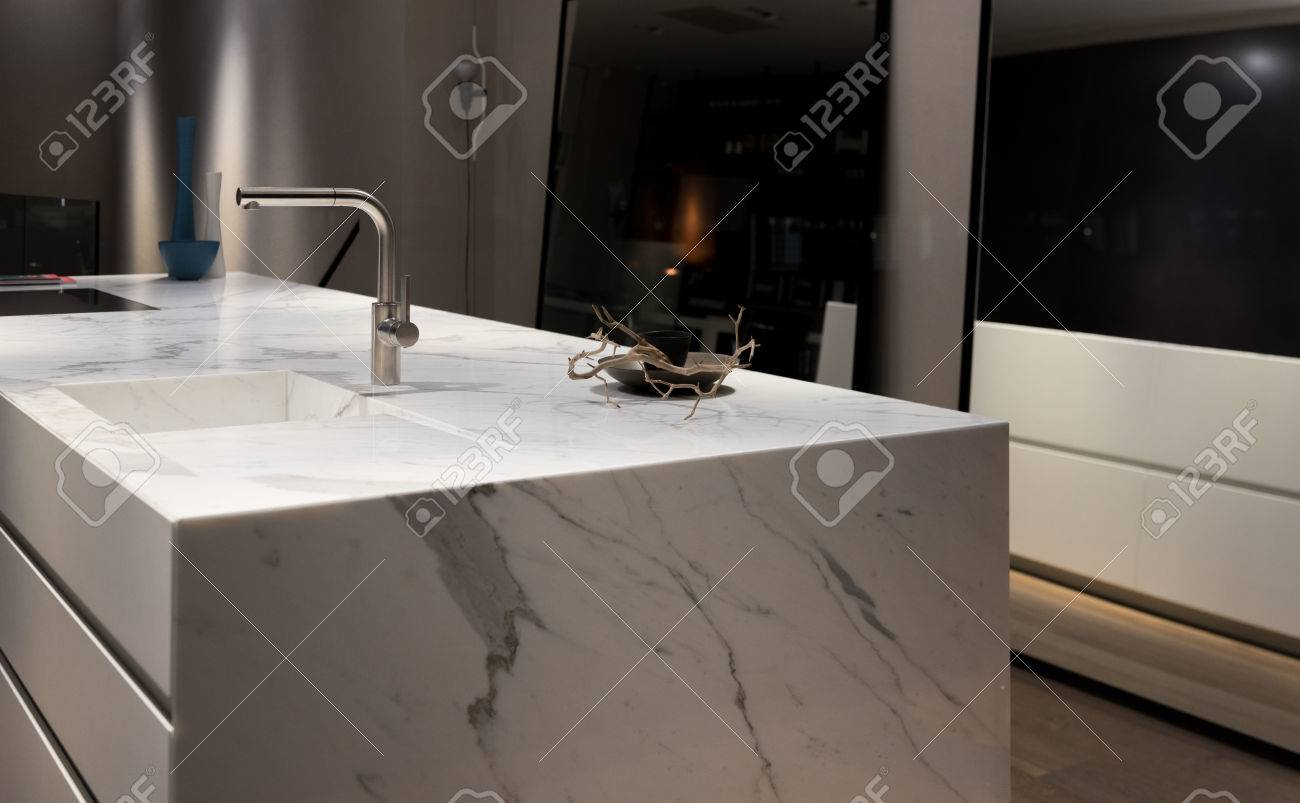 Stylish Solid White Marble Kitchen Counter With Dark Cupboards Stock