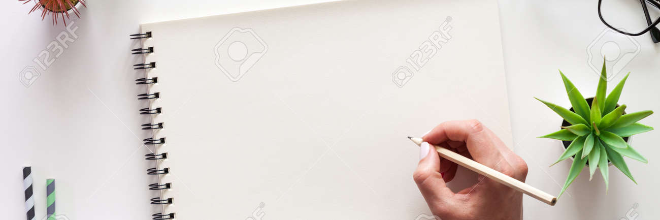 A white desk with an open sketchbook and a woman's hand. Drawing. View from above. Creative desk. Mockup. Panorama - 152485182