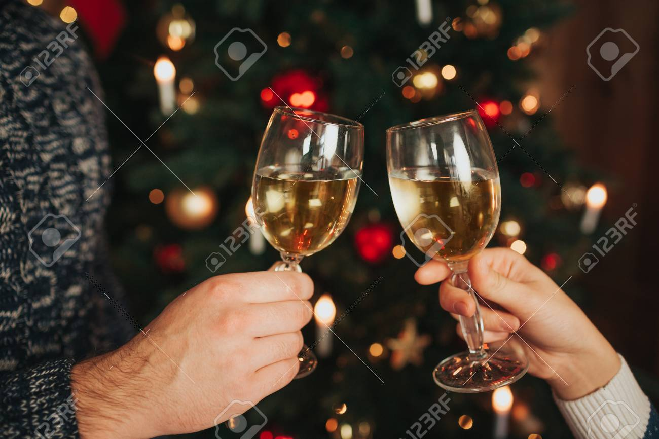 merry christmas and happy new year young couple celebrating holiday at home cheers close