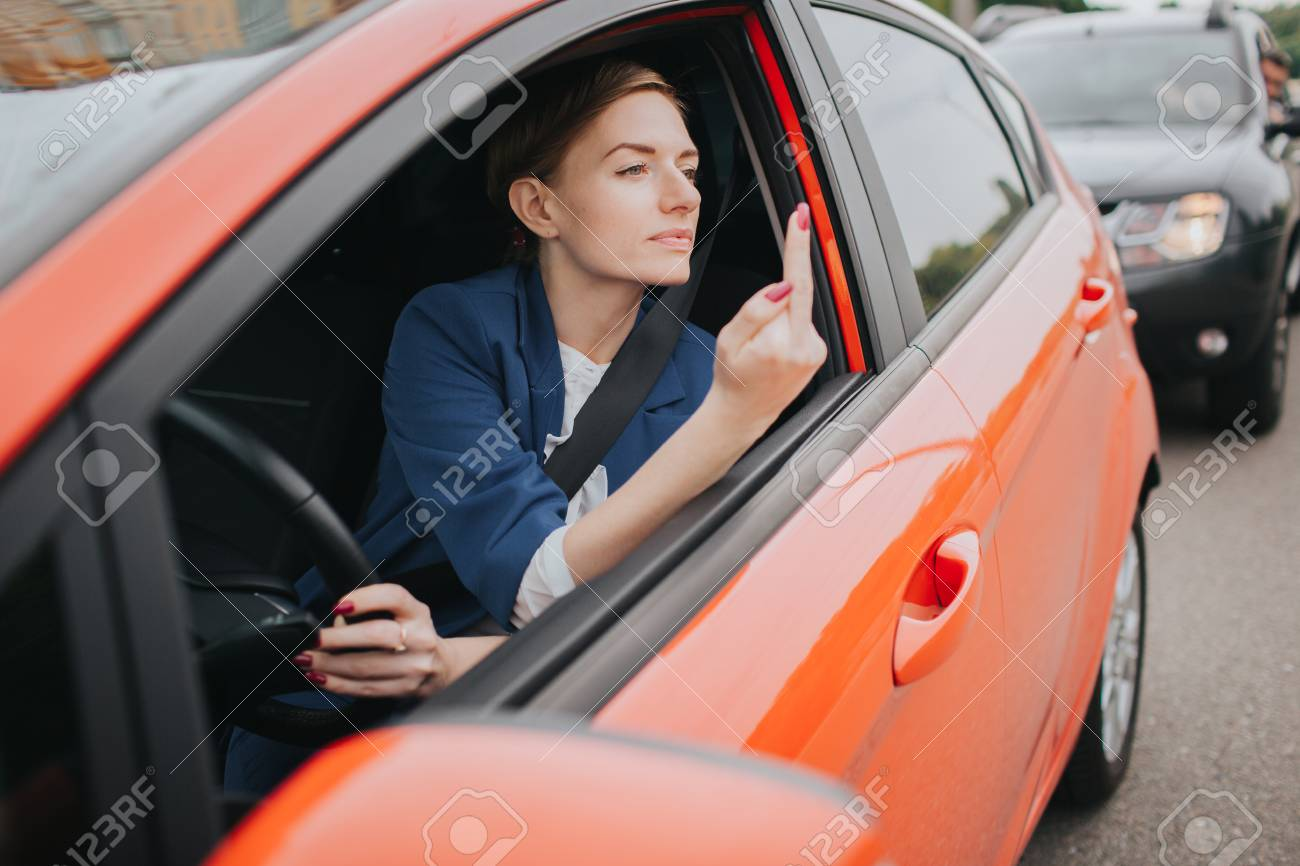A woman feels stress on the road. Shows the fact in the window. Big Traffic jams. Business woman is late for work - 91965327