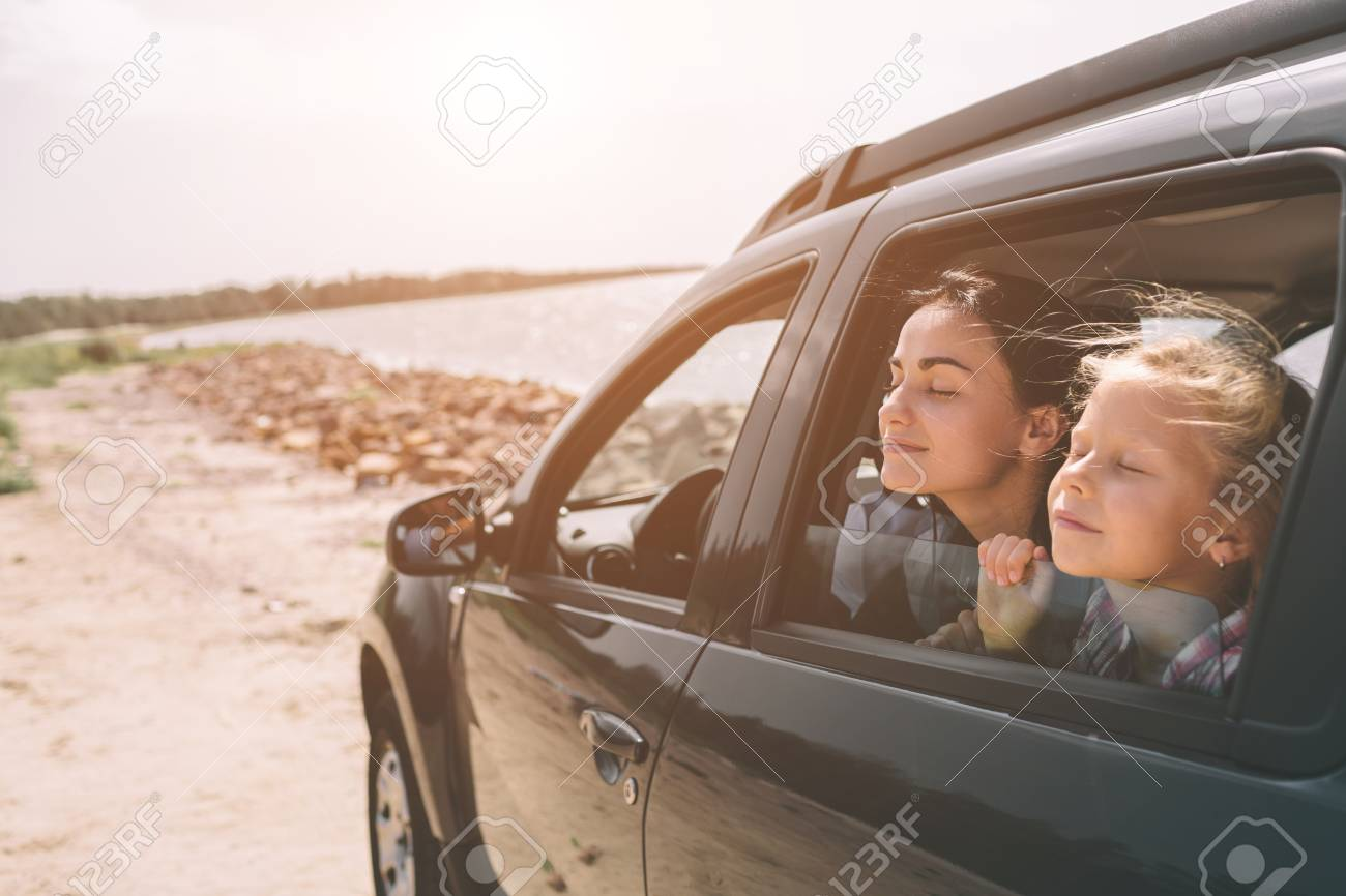 Happy family on a road trip in their car. Dad, mom and daughter are traveling by the sea or the ocean or the river. Summer ride by automobile. - 119521380