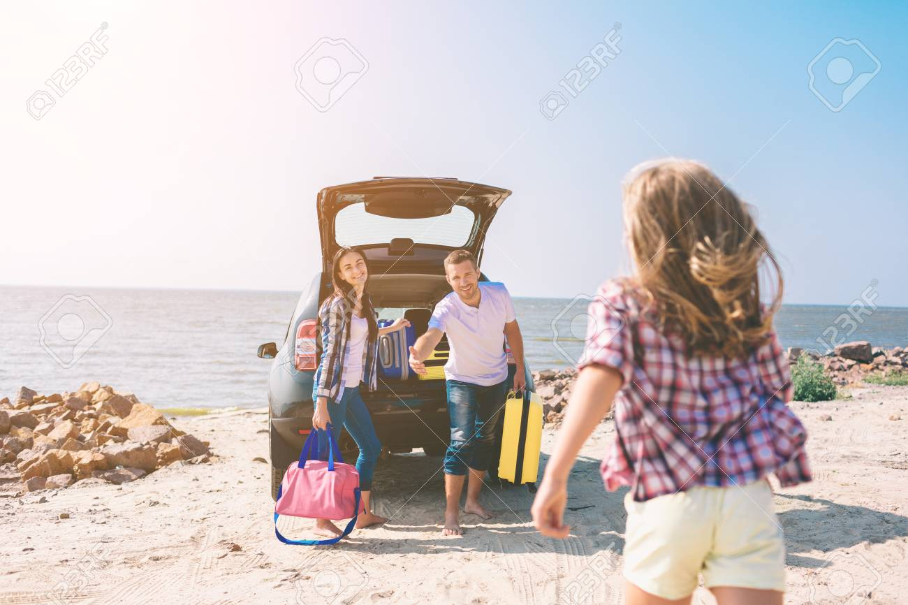 Young couple standing near the opened car boot with suitcases and bags. Dad, mom and daughter are traveling by the sea or the ocean or the river. Summer ride by automobile - 119521383