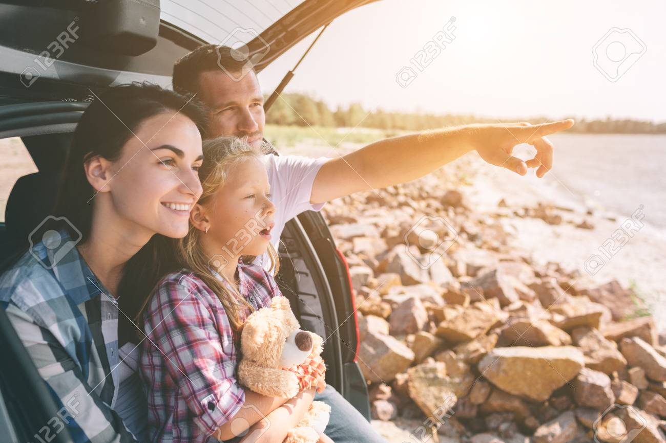 Happy family on a road trip in their car. Dad, mom and daughter are traveling by the sea or the ocean or the river. Summer ride by automobile - 119511805