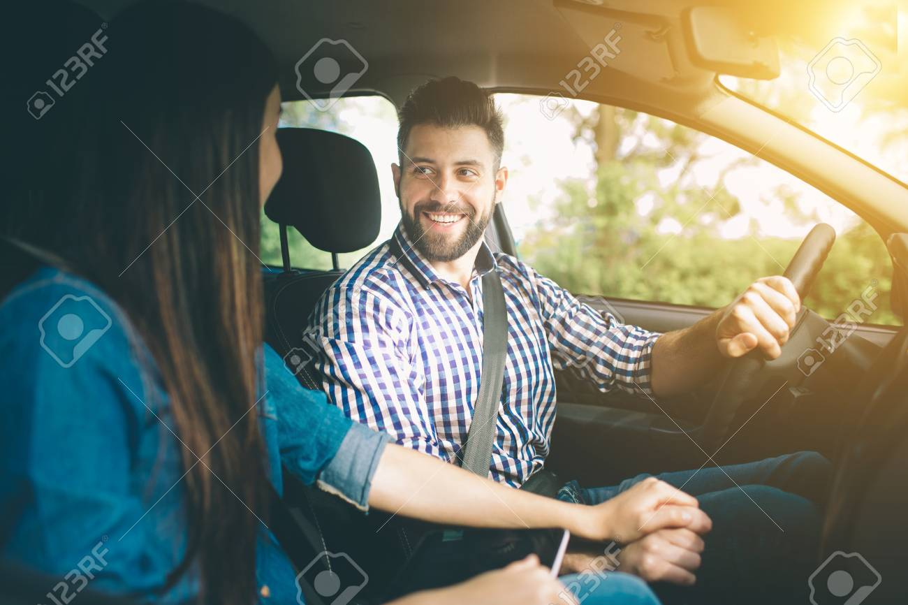 Careful driving. Beautiful young couple sitting on the front passenger seats and smiling while handsome man driving a car - 92879647