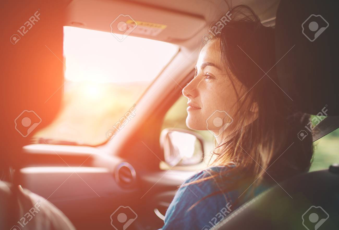 Beautiful woman smiling while sitting on the front passenger seats in the car - 92909340