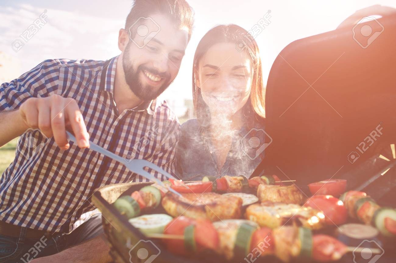 Friends making barbecue and having lunch in the nature. Couple having fun while eating and drinking at a pic-nic - Happy people at bbq party. - 92937388