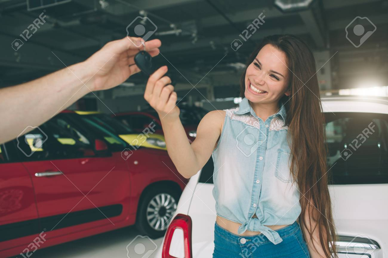 Beautiful young woman is holding a key in car dealership. Auto business, car sale, - happy female model in auto show or salon - 93198807