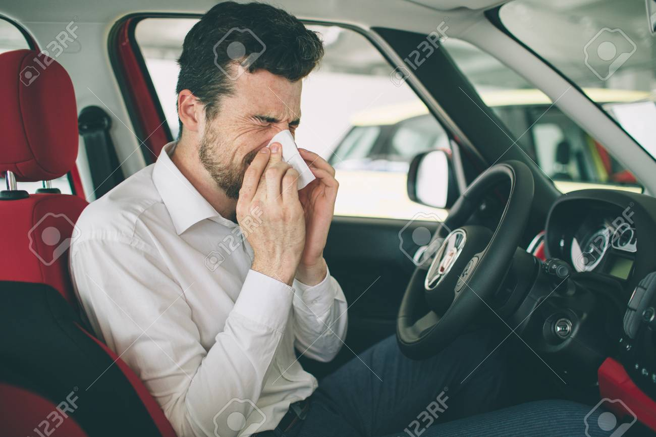 from a young man with handkerchief. Sick guy has runny nose. man makes a cure for the common cold in the car - 93304108