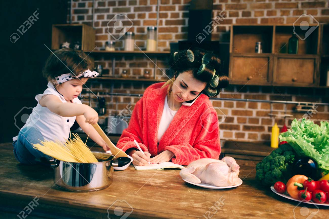Stressed mum at home. Young mother with little child in the home kitchen. Woman doing many tasks while looks after her baby - 93442178