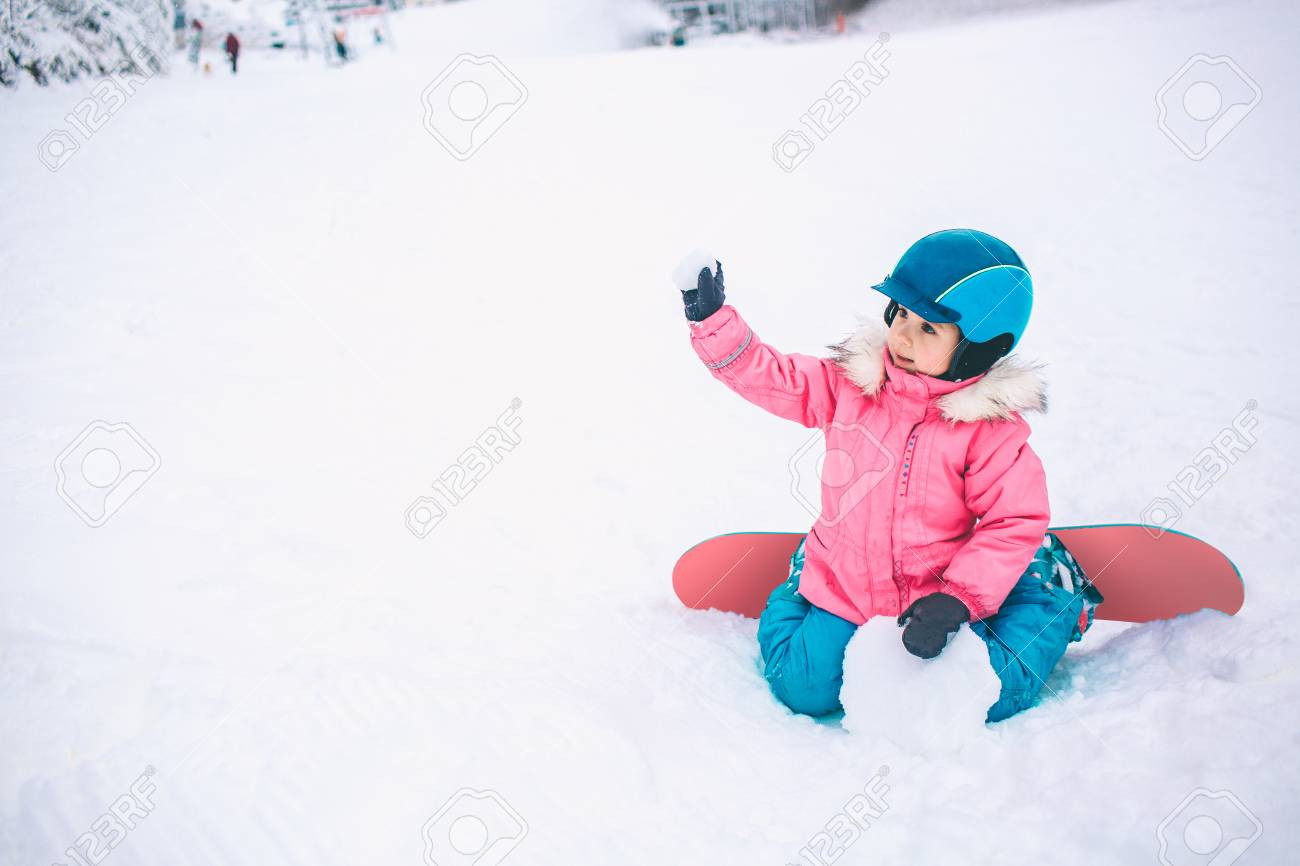 Snowboard Winter Sport. Little kid girl playing with snow wearing warm winter clothes. Winter background - 94247915