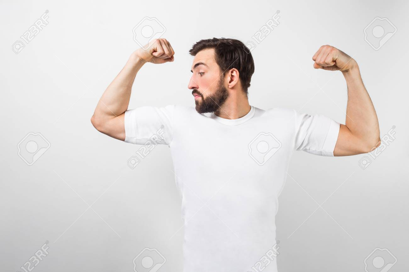4395c6bab A handsome confident young man standing and showing big muscles on his hands.  Stock Photo