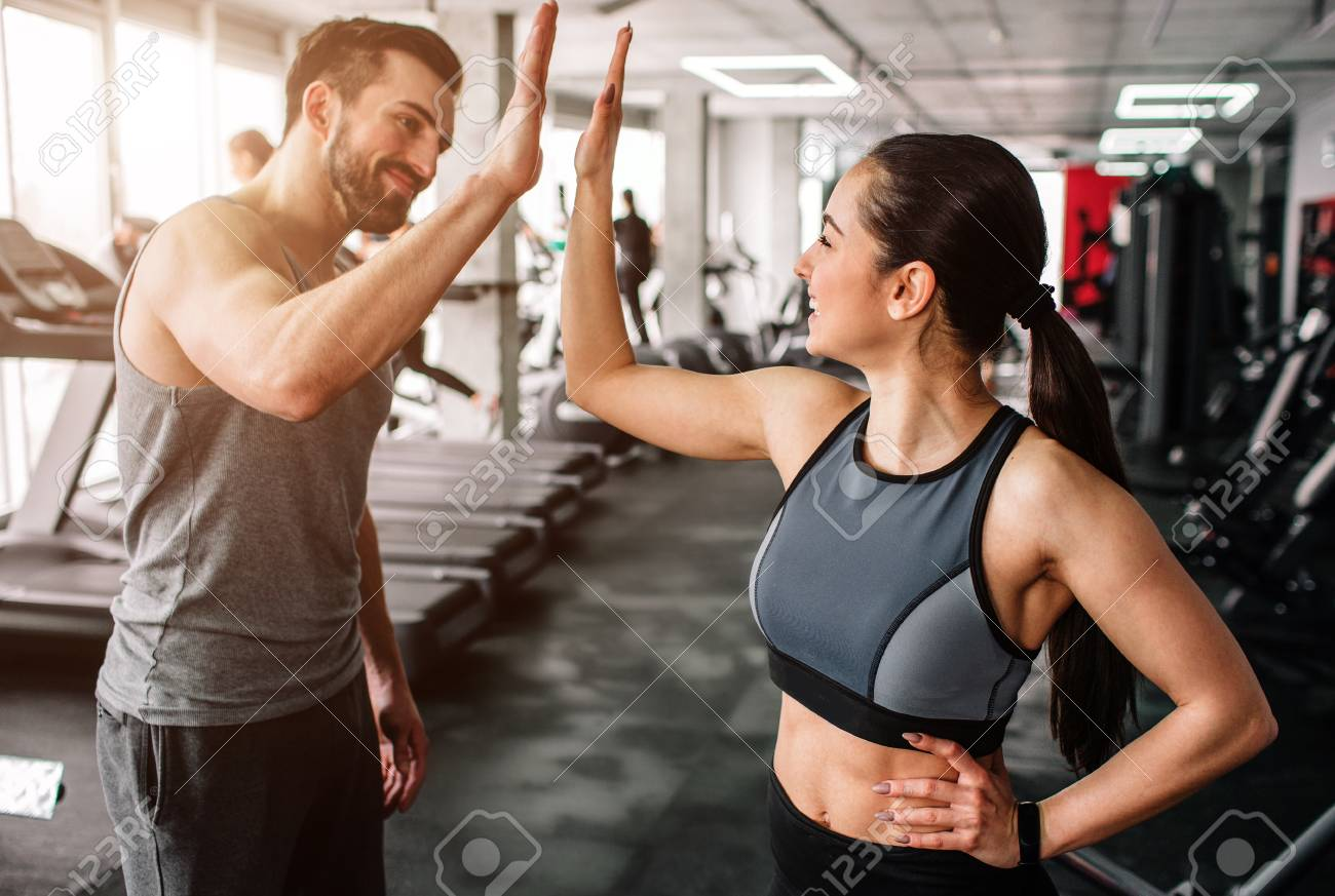 A beautiful girl and her well-built boyfriend are greeting each other with a high-five. They are happy to see each othr in the gym. Young people are ready to start their workout. - 97145284