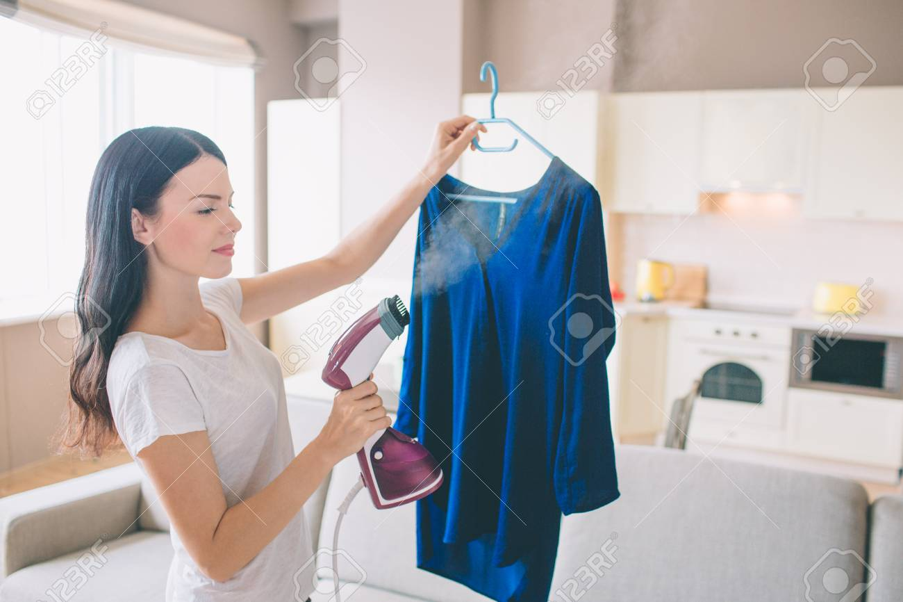 Woman is steaming blue shirt in room. She holds small stream iron in hand. Brunette is concentrated on work. - 108059929