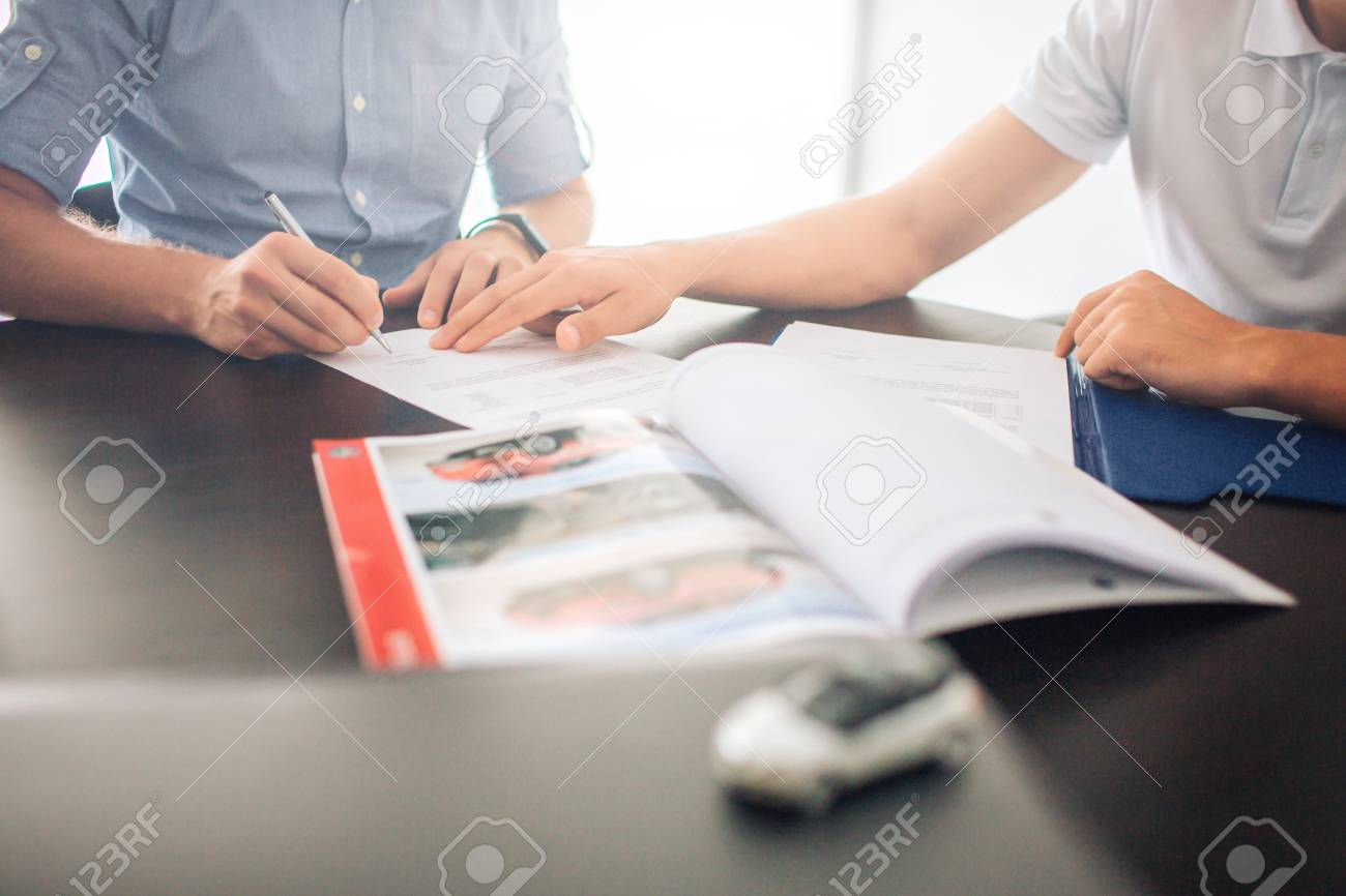 Two men sit at table. Guy on left signing papers while man on left points with hand. There is opened journal in front of them. Also there is small white car toy. - 110162629