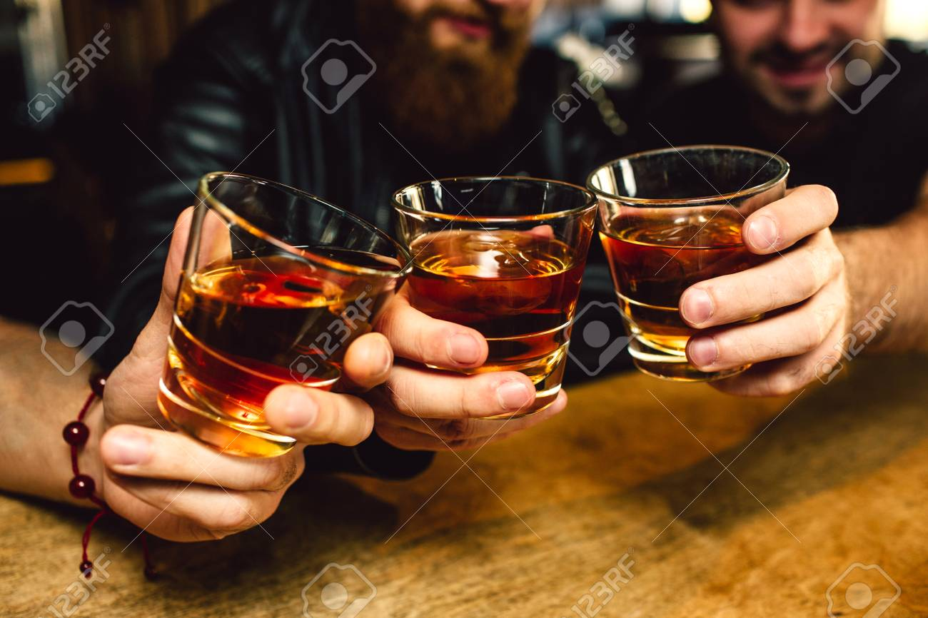 Cut view of three bearded young men holding glasses with rum together. They smile. People sit in bar - 119519705