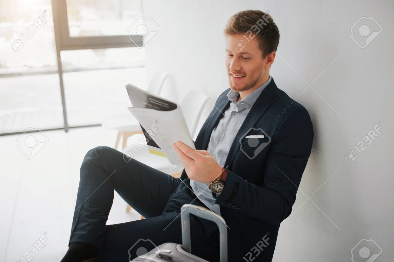 Cheerful young businessman sit on chair in white room. He read newspaper and smile. Guy wait for flight. - 115898175