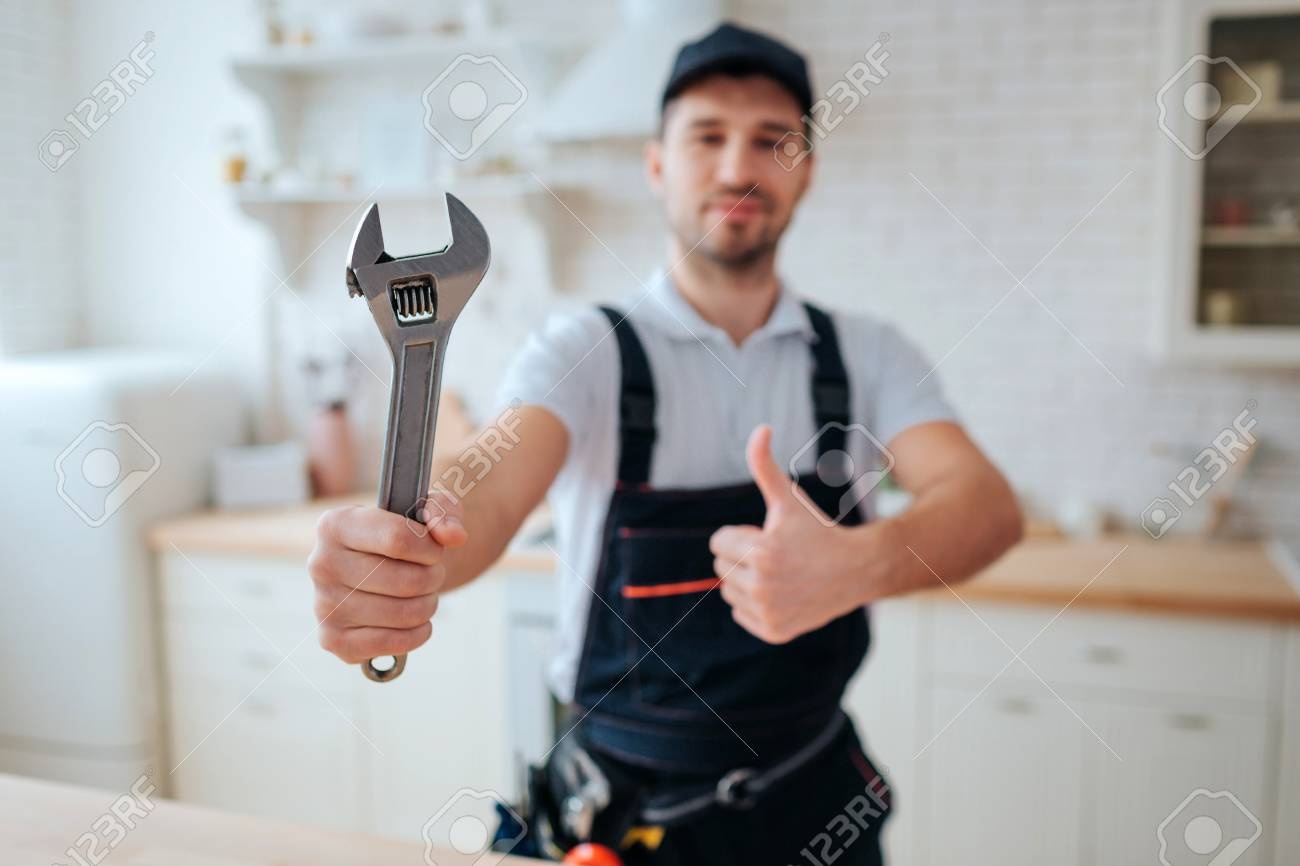 Young plumber hold wrench in hand. He show it to camera and hold big thumb up. Guy stand in kitchen. White background. Daylight - 118701911