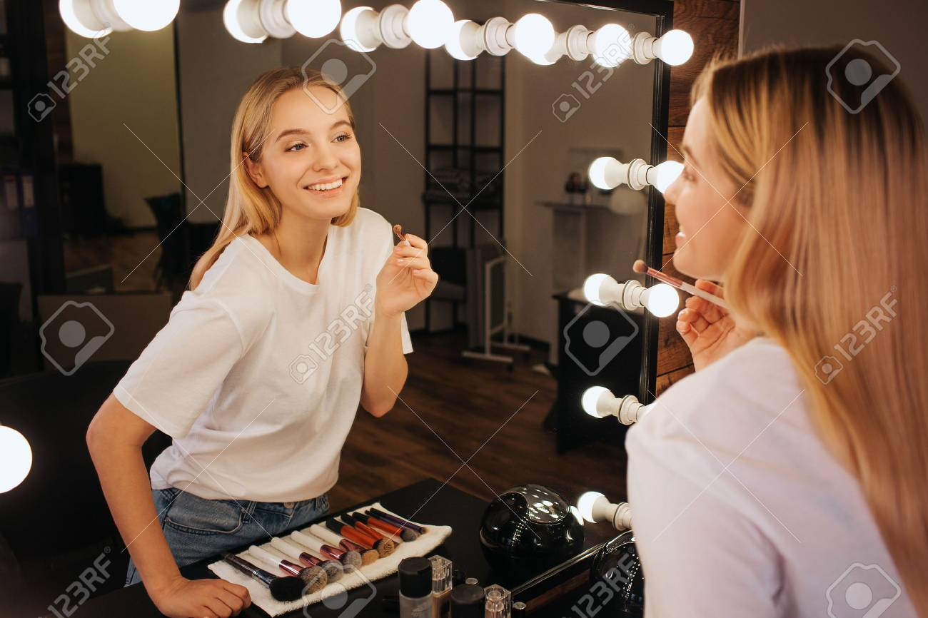 Nice cheerful young woman look in mirror in beauty room and smile. She hold brush for eyeshadows. - 118702577