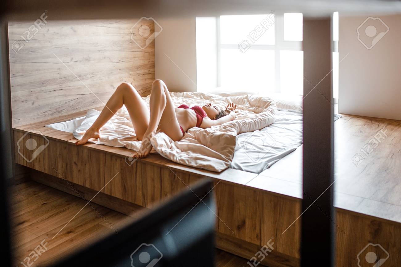 Seductive young dark-haired woman in bed on morning. Slim hot model lying alone. Well-built beautiful legs. Woman wear red lingerie. Masturbation. Sensual picture. - 125120426