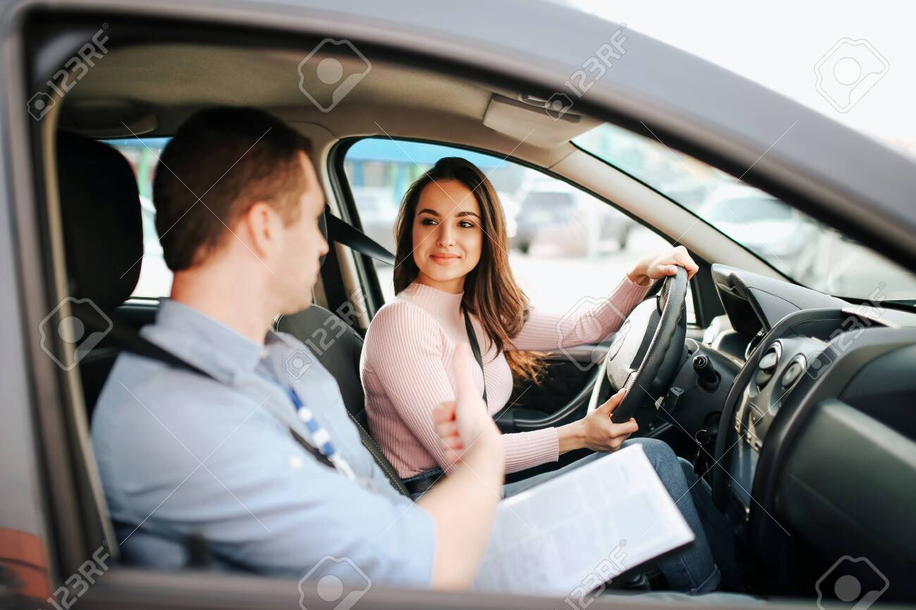 Male auto instructor takes exam in young woman. Positive happy model look at guy and smile. Driving car alone and careful. Guy talks to her. Passing exam. - 131750962
