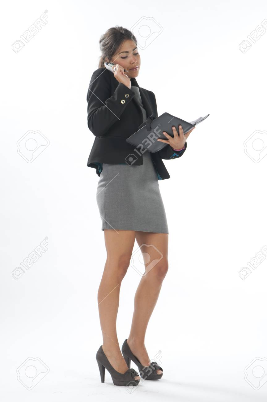 Bussy young executive female, talking on the phone and writing on her notebook. Stock Photo - 14429716
