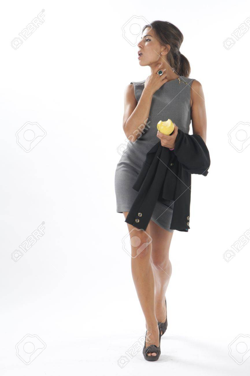 Full length healthy young business executive woman, on white, looking away, walking holding an apple. Stock Photo - 14429636