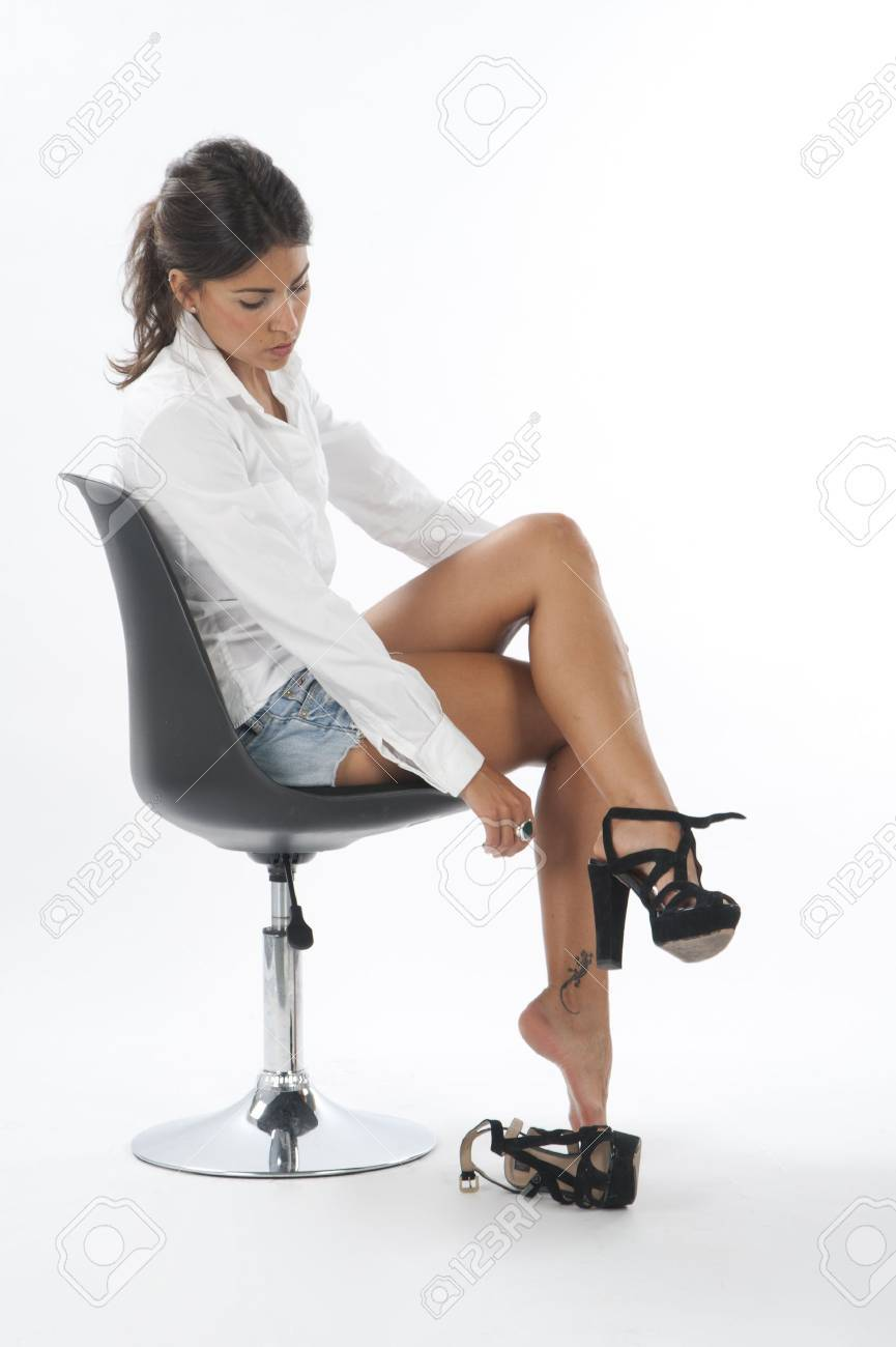 Serious young girl on white, trying on pair of shoes Stock Photo - 14429762