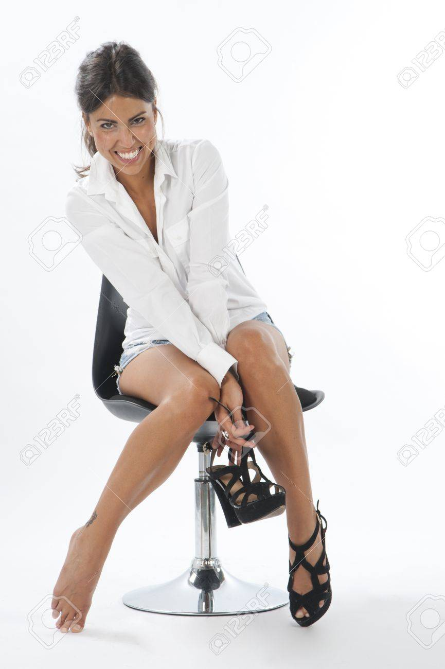 Happy young girl on white, with pair of shoes in her hands. Stock Photo - 14429781