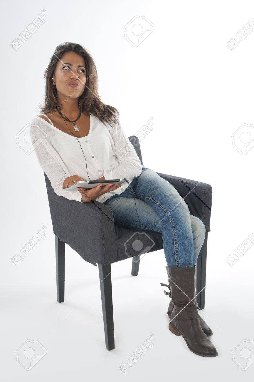 Young girl daydreaming, wearing casual clothing, on white, sitting on sofa holding tablet PC. Stock Photo - 14591121