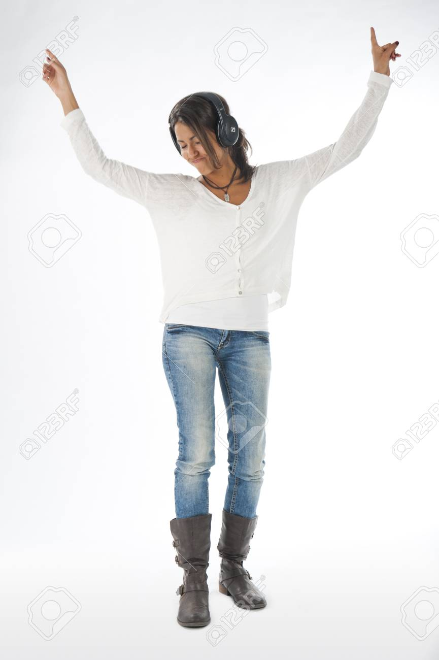 Full length portrait of young girl, on white, wearing casual clothing, enjoying music with hands up and head phones Stock Photo - 14938078