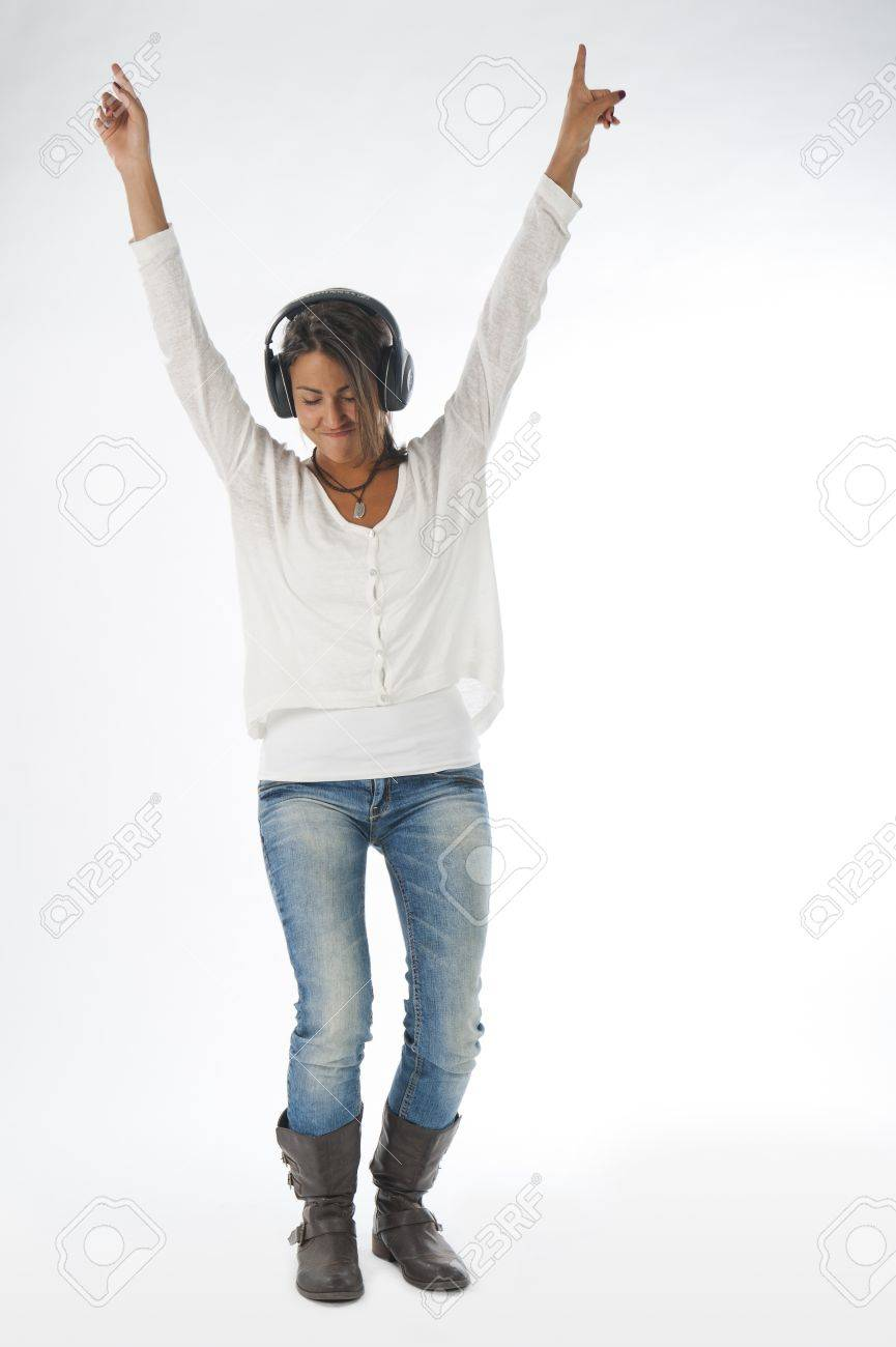 Full length portrait of young girl, on white, wearing casual clothing, enjoying music with hands up and head phones Stock Photo - 14938076