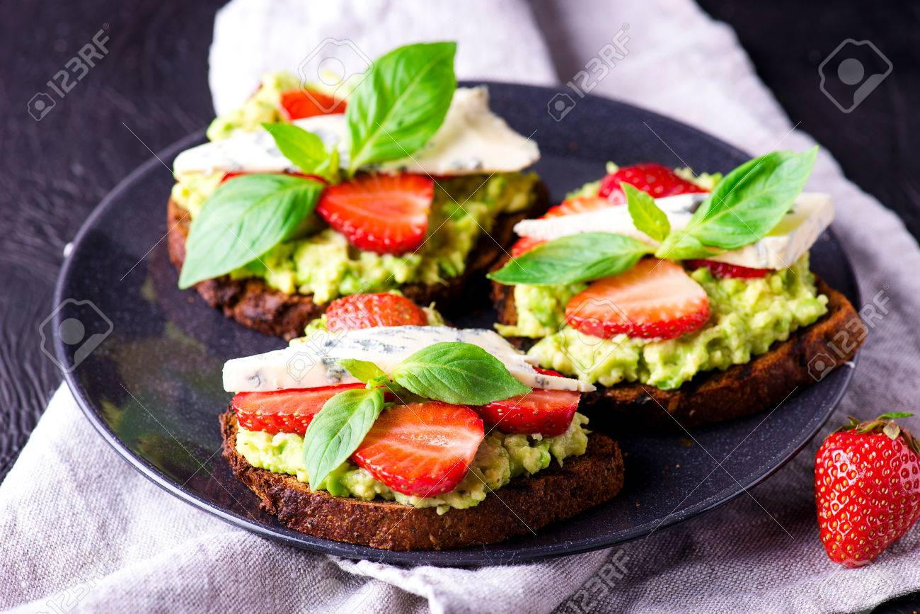 Fresh toast with strawberry on dark plate - 58050369