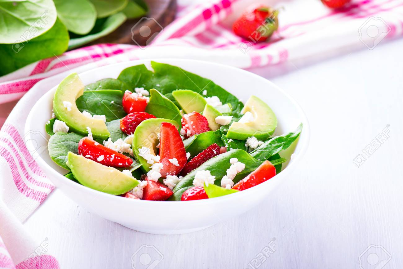 Summer salad with strawberry, avocado and spinach. White table. - 58050380