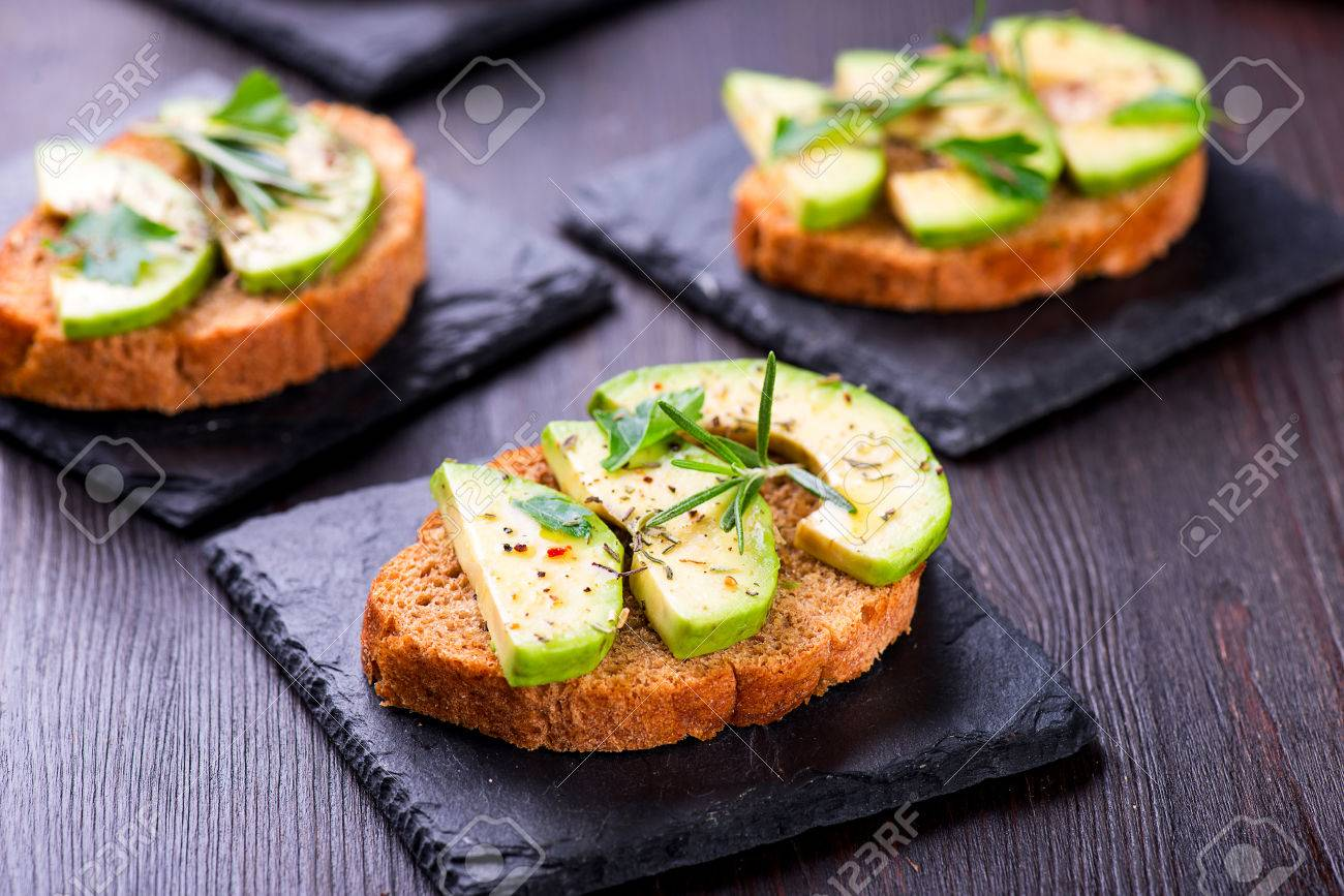 Toast with rye bread and avocado, herbs on slate board - 58050393
