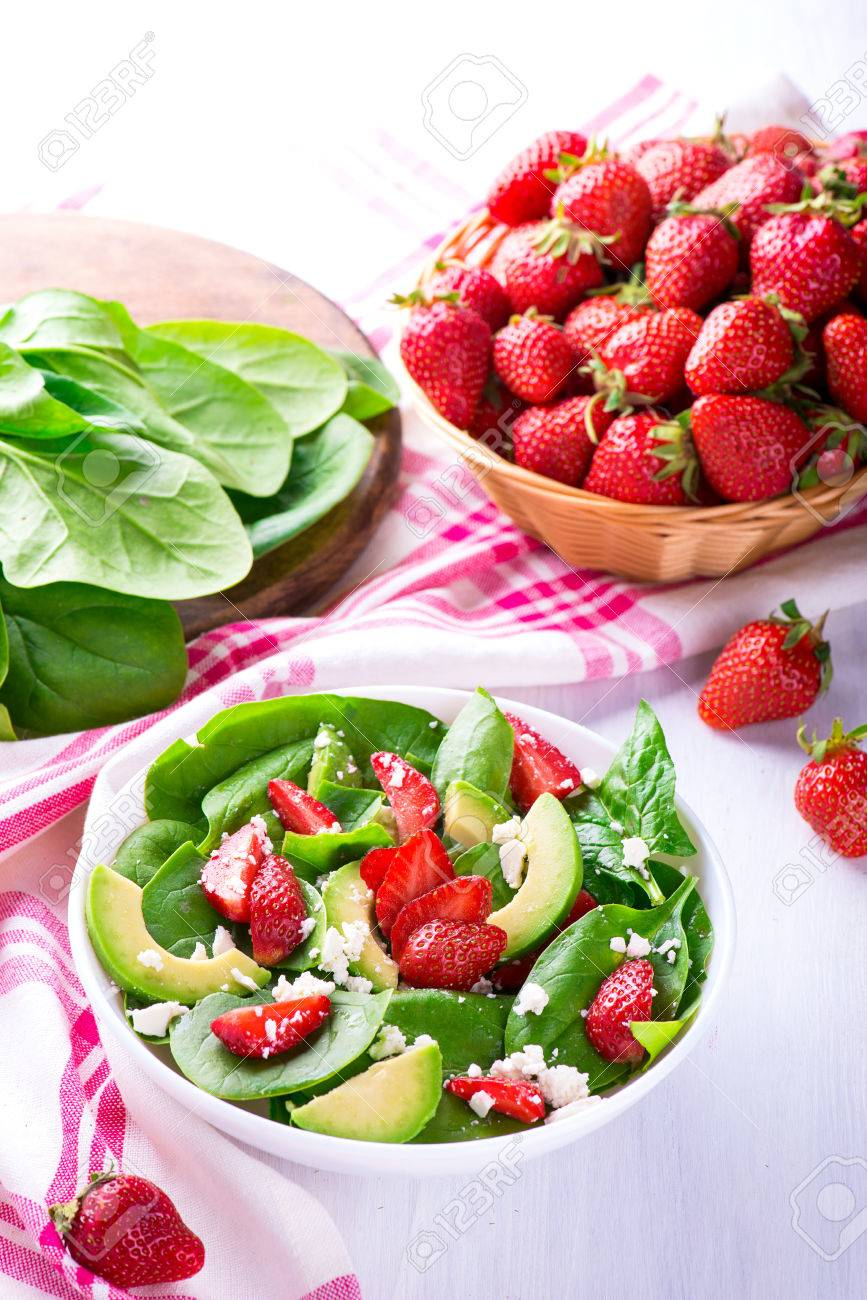 Summer salad with strawberry, avocado and spinach. White table. - 58050405