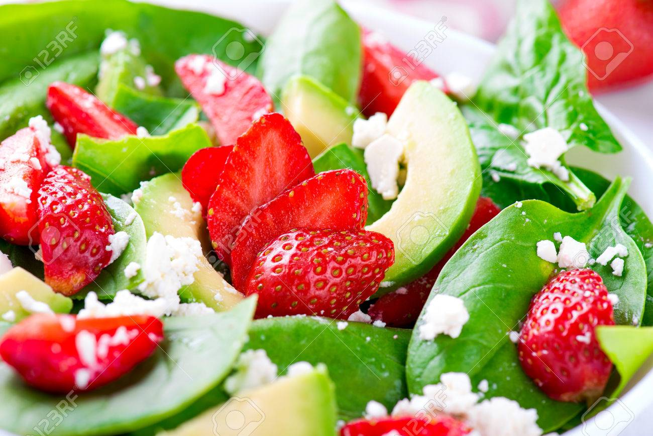 Summer salad with strawberry, avocado and spinach. White table. - 58050423