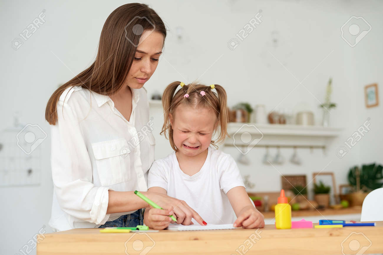 Kind mother embracing and comforting small crying daughter having difficulties with homework while sitting at table and doing exercise in copybook in kitchen. Help with homework - 169489260
