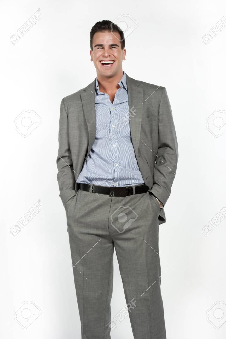 hot sale online ce071 f96be Atletico e attraente maschio caucasico che indossa un abito grigio aderente  con un pulsante blu giù camicia in un ambiente su uno sfondo bianco in ...